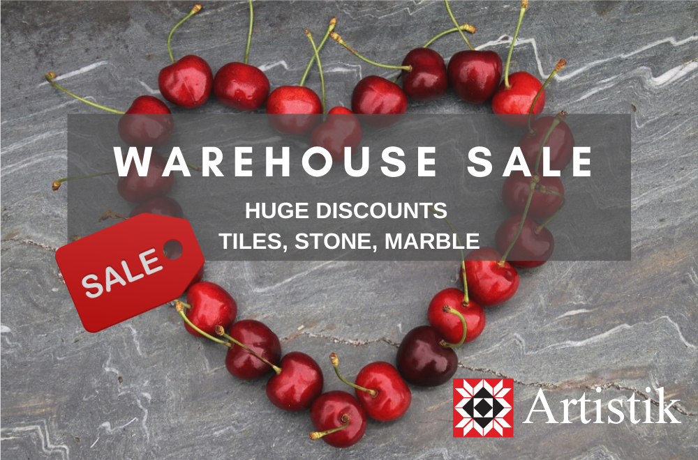 A grey tile background with red cherries in the shape of a heart. It is promoting a special offer on tiles and natural stone for a supplier named Artistik Stone.